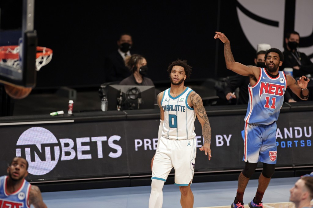 Brooklyn Nets guard Kyrie Irving (11) watches his 3-pointer, next to Charlotte Hornets forward Miles Bridges during the first half of an NBA basketbal...
