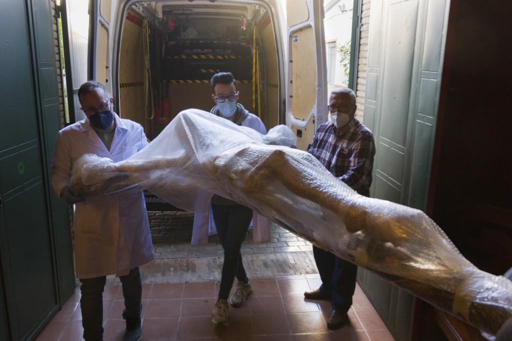A restored figure of Jesus arrives into Nuestra Senora de la Candelaria church in Seville, southern Spain, Thursday, March 25, 2021. Few Catholics in ...