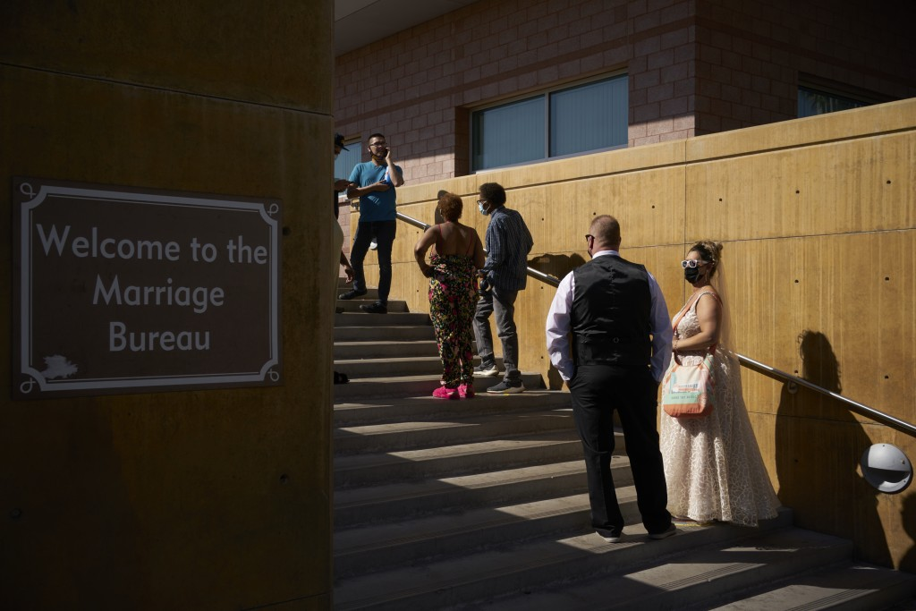 Couples wait in line for marriage licenses at the Marriage License Bureau, Friday, April 2, 2021, in Las Vegas. The bureau was seeing busier than norm...