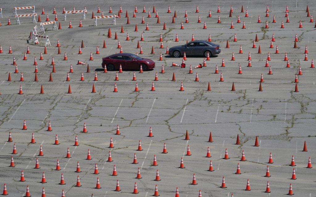 Vehicles drive around in opposite directions in a maze of traffic cones, as they enter the Dodgers Stadium vaccination site in Los Angeles Friday, Apr...
