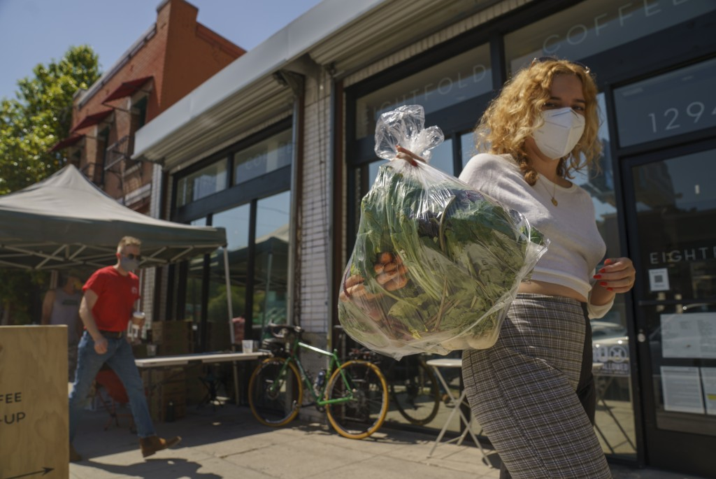 Fashion designer Josie Vand wears a facemask as she retrieves a bag with organic vegetables from a farm box from County Line Harvest in Los Angeles on...