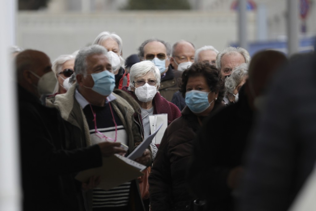FILE - In this Friday, March 19, 2021 file photo people line up to get their AstraZeneca vaccine shot at La Nuvola (The Cloud) convention center that ...