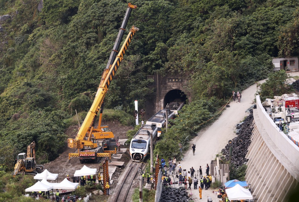 Rescue workers remove a part of the derailed train near Taroko Gorge in Hualien, Taiwan on Saturday, April 3, 2021. The train partially derailed in ea...