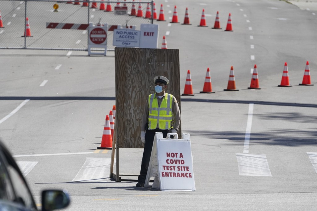 A Los Angeles Traffic control officer directs vehicles to an alternative entrance to the Dodgers Stadium vaccination site in Los Angeles Friday, April...