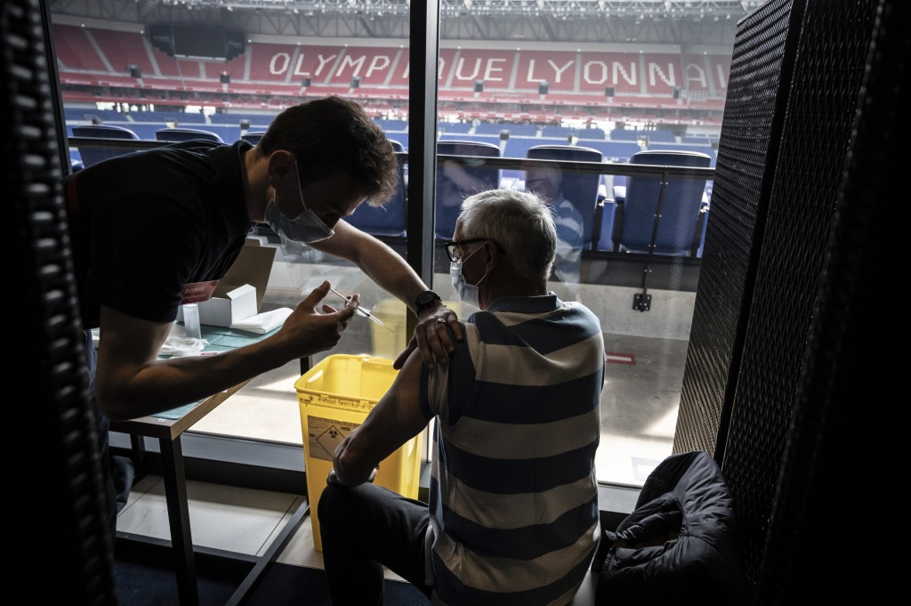 Patients receive an injection of the Moderna Covid-19 vaccine on the opening day of a mass vaccination centre set up in the Olympique Lyonnais soccer ...