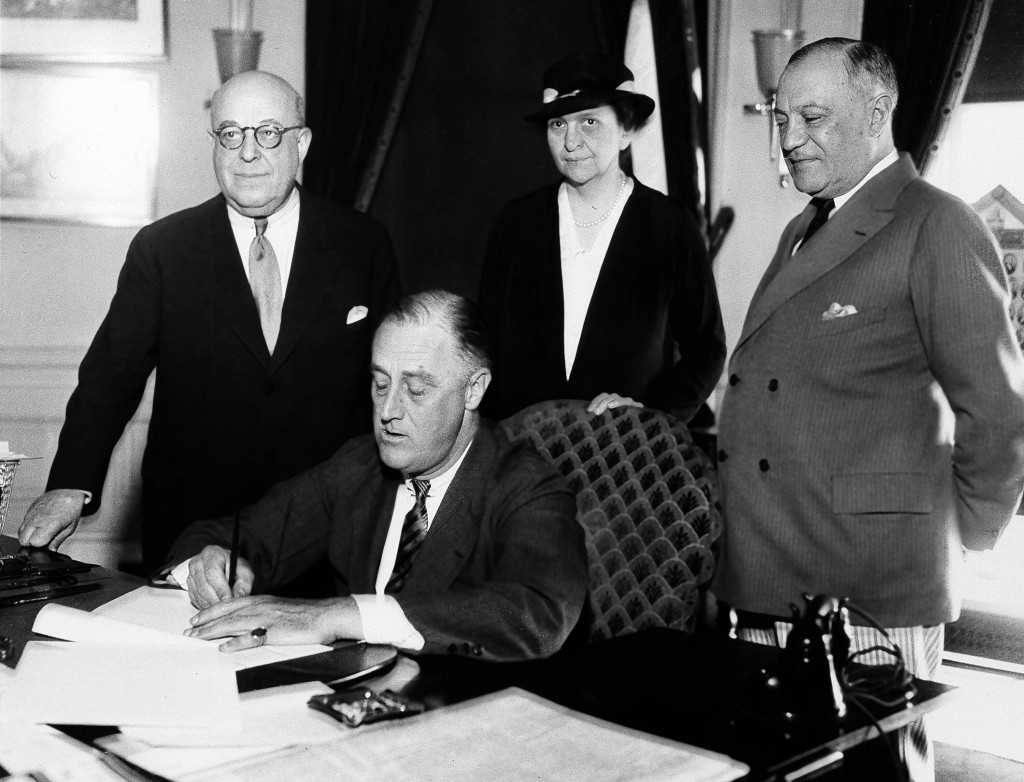 FILE - In this June 6, 1933 file photo, President Franklin D. Roosevelt is shown signing the Wagner Unemployment Bill at the White House in Washington...