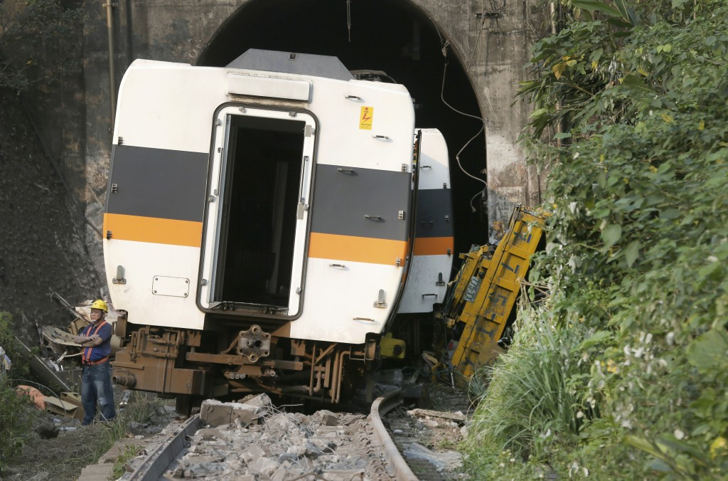 A worker stands in front of the derailed train near Taroko Gorge in Hualien, Taiwan on Saturday, April 3, 2021. The train partially derailed in easter...