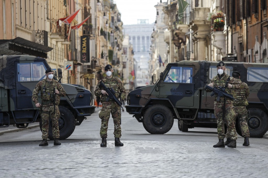 Italian Army officers patrol Rome's central Piazza del Popolo, Saturday, April 3, 2021. Italy went into lockdown on Easter weekend in its effort to ba...