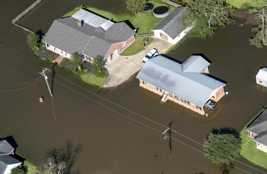 FILE - In this Oct. 10, 2020 file photo, houses surrounded by flood waters are seen in the aftermath of Hurricane Delta Saturday  in Welsh, La.  Hurri...