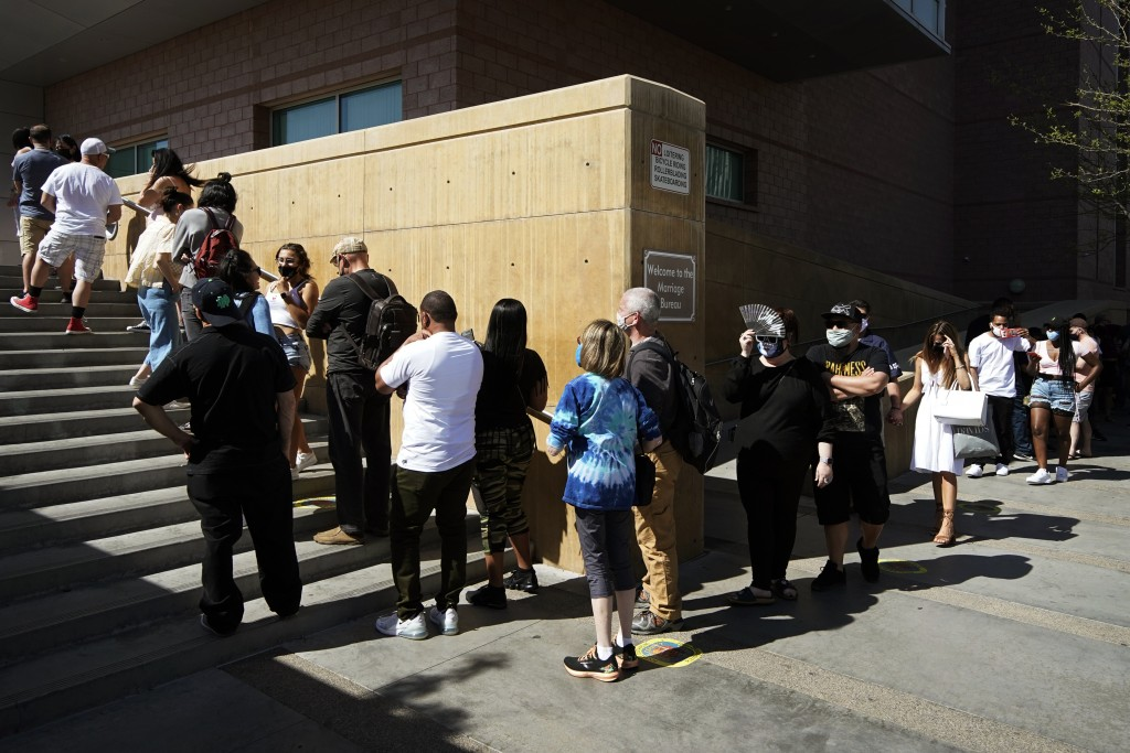 People wait in line for marriage licenses at the Marriage License Bureau, Friday, April 2, 2021, in Las Vegas. The bureau was seeing busier than norma...