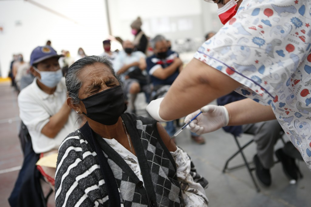 Maria Castrejon, 71, grimaces as she is vaccinated with a second dose of the Sinovac COVID-19 vaccine at the Americas Cultural Center, in Ecatepec, Me...
