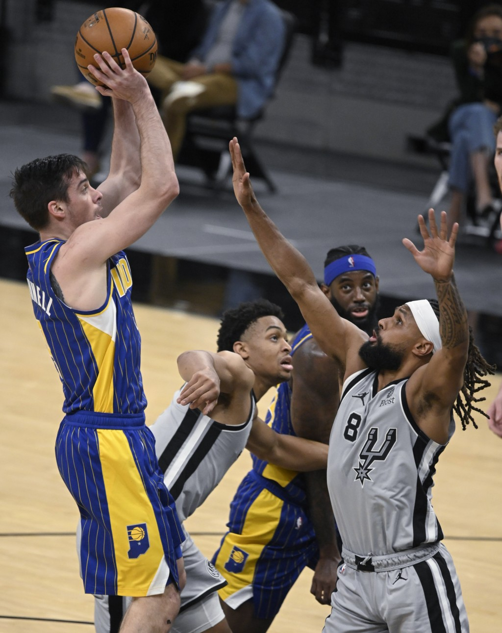 Indiana Pacers' T.J. McConnell, left, shoots against San Antonio Spurs' Patty Mills (8) as Spurs guard Keldon Johnson, second from left, and Pacers fo...