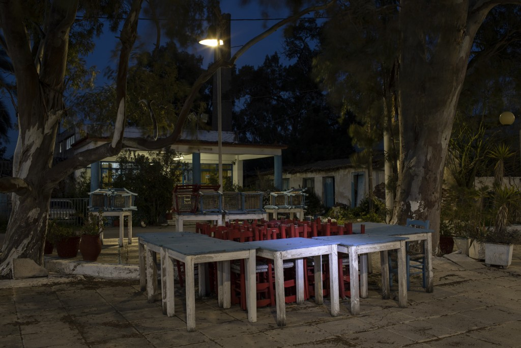 Tables and chairs stand outside a shuttered traditional fish restaurant in Aspropyrgos, a northwest suburb of Athens, on Friday, March 26, 2021. Resta...