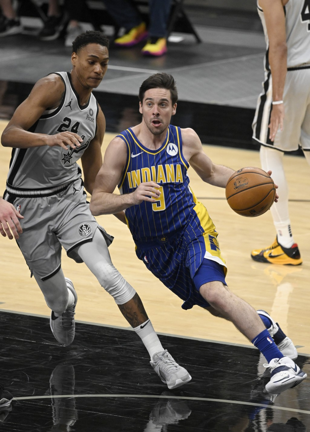 Indiana Pacers' T.J. McConnell, right, drives around San Antonio Spurs' Devin Vassell during the second half of an NBA basketball game Saturday, April...