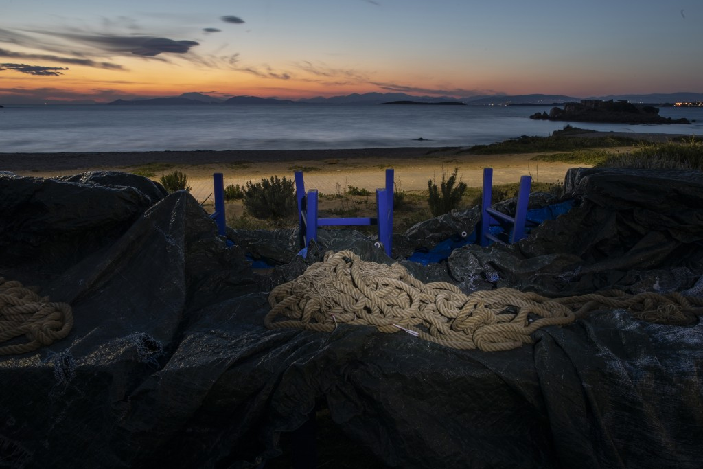 A rope used for decoration is placed on a canvas that covers tables and chairs of a shuttered fish restaurant at the seaside suburb of Kavouri, distri...