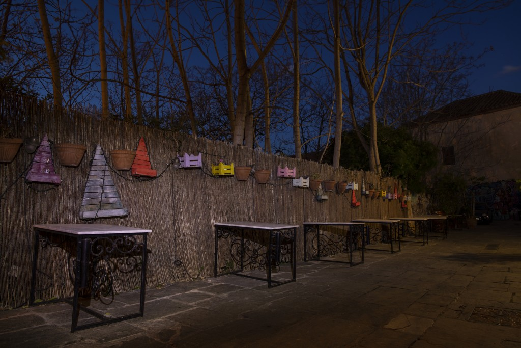 Iron tables stand in front of a decorated fence outside a shuttered traditional restaurant in Plaka, district of Athens, on Tuesday, March 16, 2021. R...