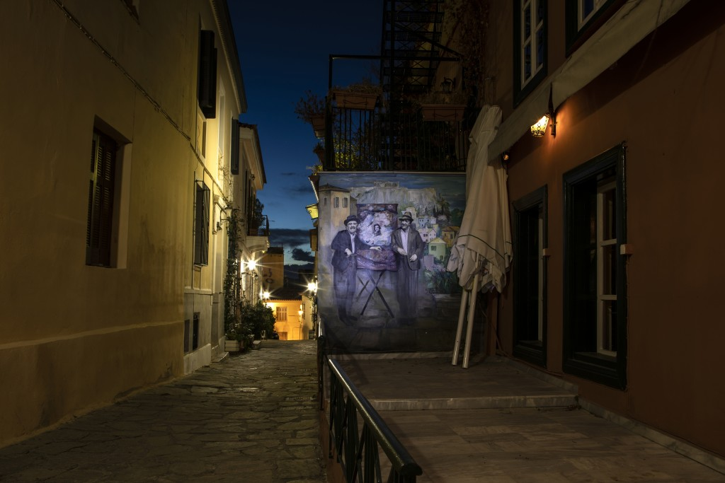Two umbrellas lean against a wall with a painting depicting a scene of an old Greek movie outside a shuttered traditional restaurant in Plaka, distric...