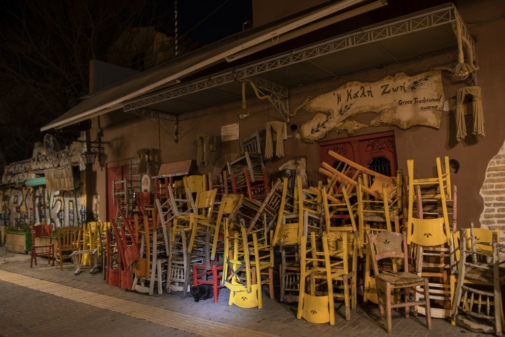 A cat stands near coloured chairs and tables stored outside a closed traditional restaurant in Monastiraki, district of Athens, on Tuesday, March 16, ...