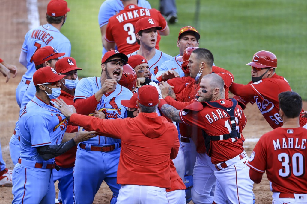 St. Louis Cardinals' Nolan Arenado, center left, reacts alongside teammate catcher Yadier Molina, center, as they scrum with members of the Cincinnati...