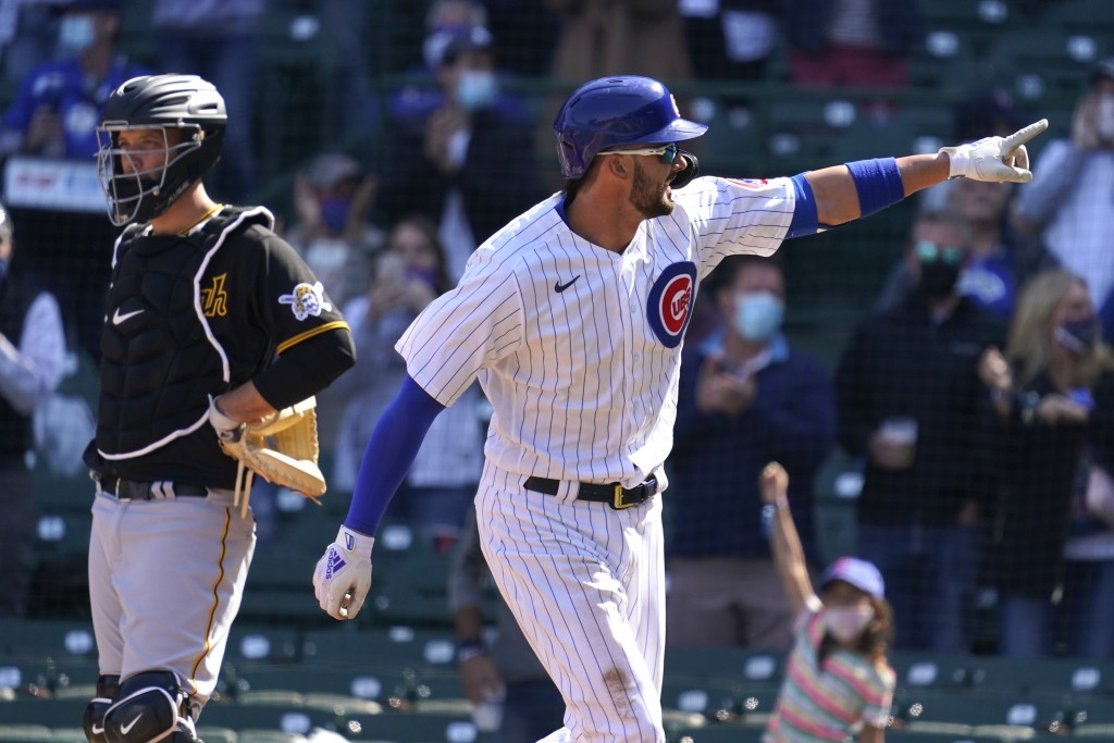 Chicago Cubs' Kris Bryant, right, points after hitting a solo home run as Pittsburgh Pirates catcher Jacob Stallings looks to the field during the thi...