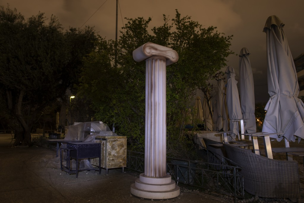 A replica of an ancient Greek column stands next to stored tables and umbrellas outside a shuttered coffee shop in Thission, district of Athens, on Th...