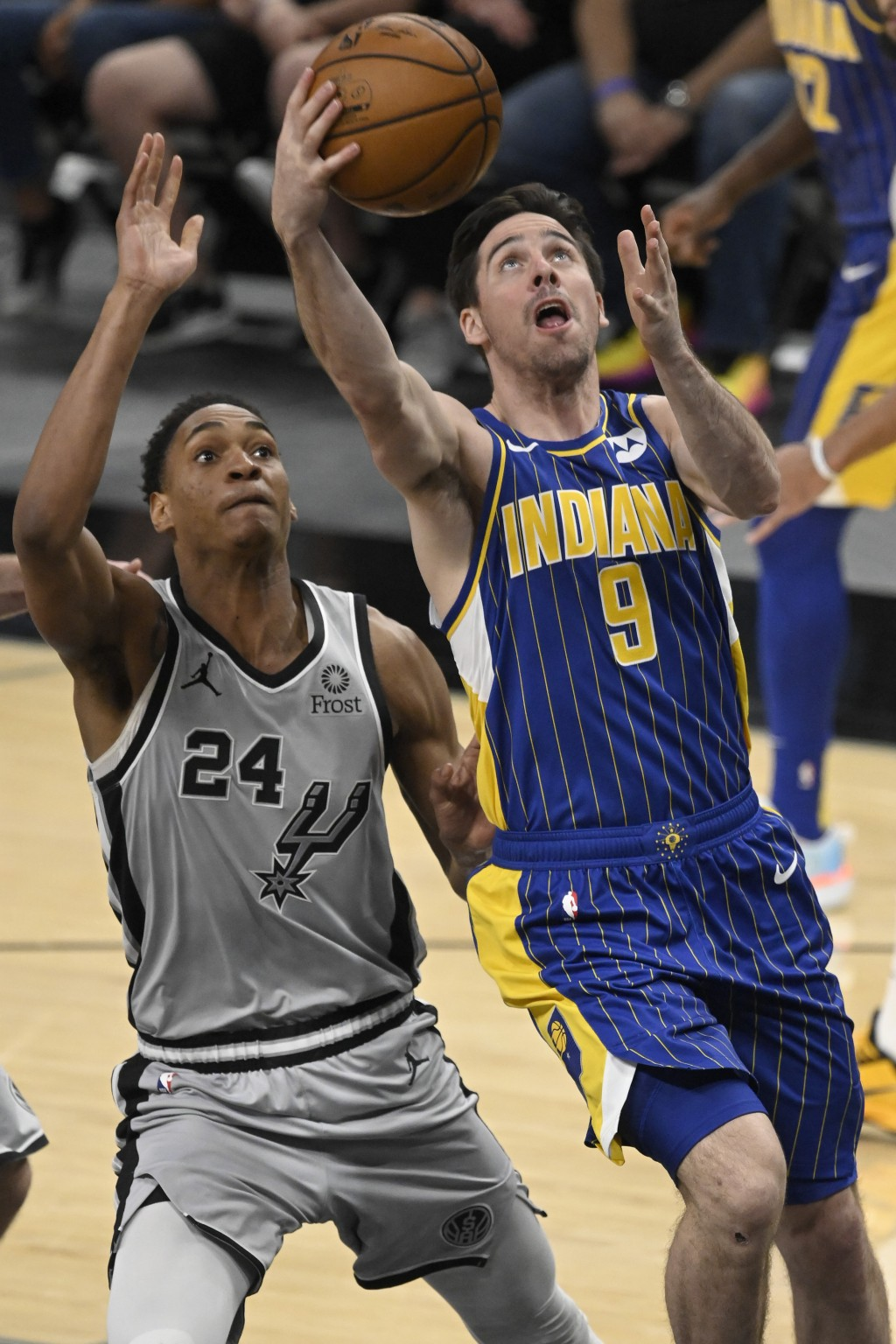 Indiana Pacers' T.J. McConnell (9) shoots next to San Antonio Spurs' Devin Vassell during the second half of an NBA basketball game Saturday, April 3,...