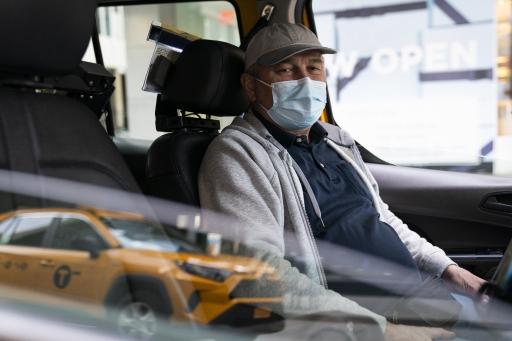 """Nicolae Hent sits for a portrait in his taxi outside a midtown Manhattan hotel, in New York on March 19, 2021. """"Not an easy year to go through in 2020..."""