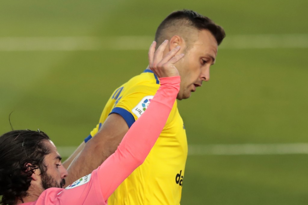 FILE - In this Oct. 17, 2020, file photo, Cadiz's Juan Cala and Real Madrid's Isco, left, fight for possession during the Spanish La Liga soccer match...