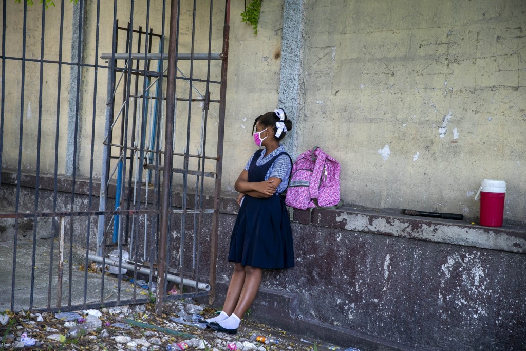 FILE - In this Aug. 17, 2020 file photo, a student waits for her turn to enter the Lycee Marie Jeanne school on the first day back to school since the...
