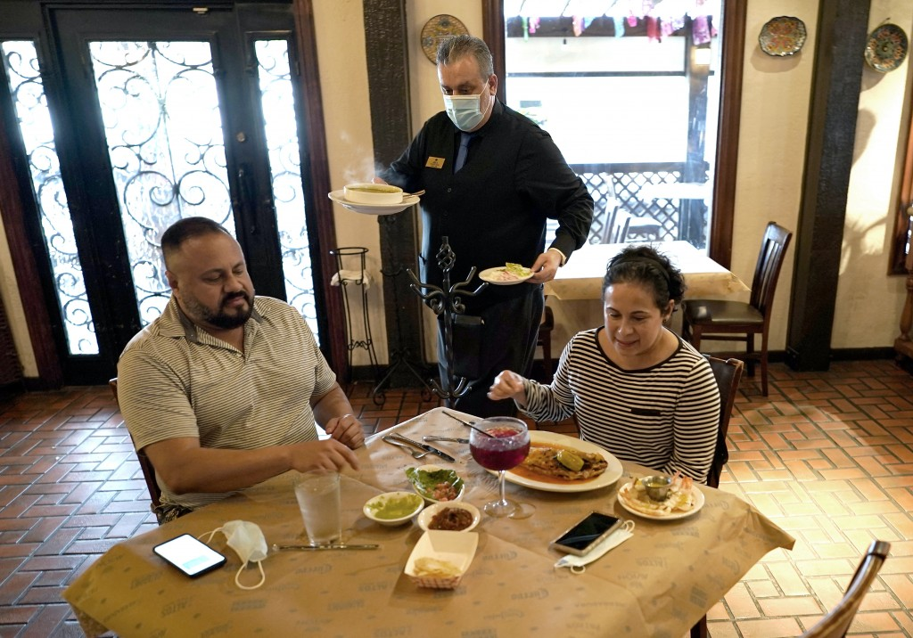 FILE - In this Wednesday, March 10, 2021 file photo, waiter Jose Bravo, center, delivers food for Alberto Castaneda, left, and his wife, Esther, at Pi...