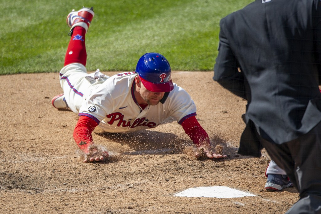 Philadelphia Phillies first baseman Rhys Hoskins (17) slides into home plate to score on an RBI single by Alec Bohm during the eighth inning of a base...