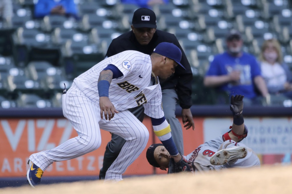 Minnesota Twins' Andrelton Simmons (9) slides in safely at third base past the tag of Milwaukee Brewers' Orlando Arcia during the eighth inning of a b...