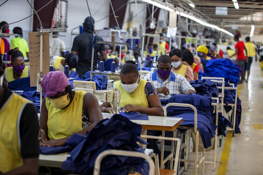 FILE - In this April 21, 2020 file photo, factory workers sew medical clothing and face masks at the Sonapi Industrial Park in Port-au-Prince, Haiti. ...