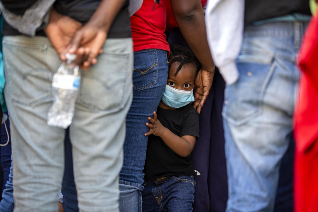 FILE - In this April 23, 2020 file photo, a child looks at the camera as Haitians who were deported from the U.S. line up as they arrive at a hotel wh...