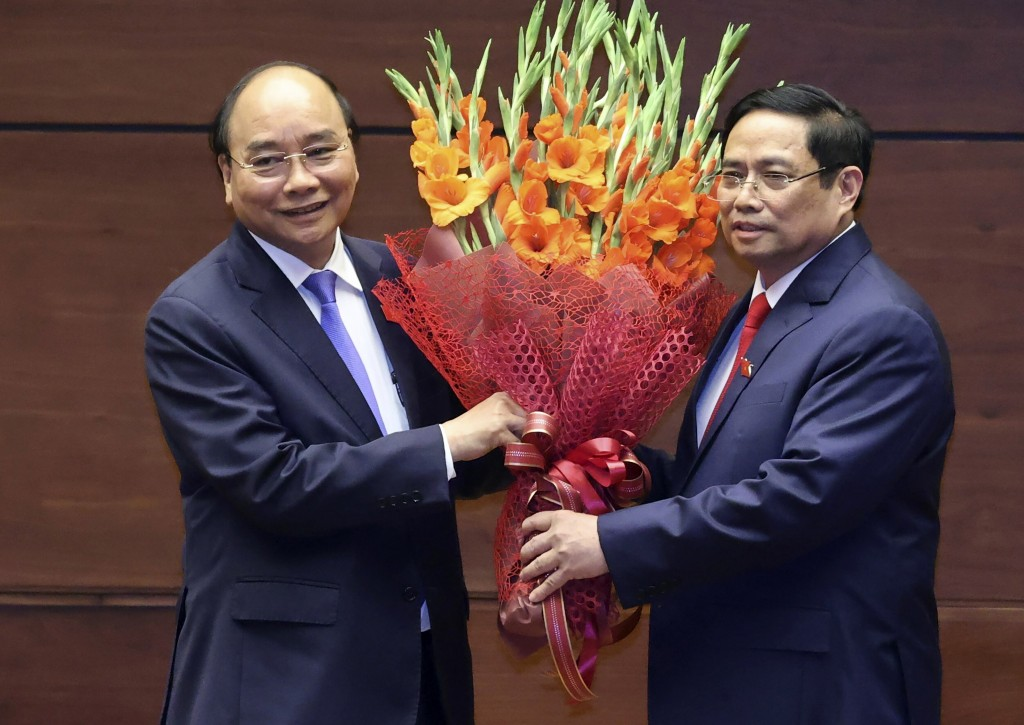 Vietnamese newly elected President Nguyen Xuan Phuc, left, and newly elected Prime Minister Pham Minh Chinh pose for a photo in the National Assembly ...