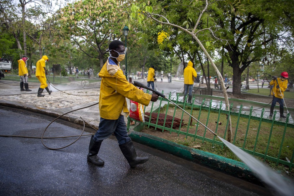 FILE - In this April 7, 2020 file photo, City Hall workers spray disinfectant in the street and a park in Petion-Ville, Haiti. To help contain the spr...