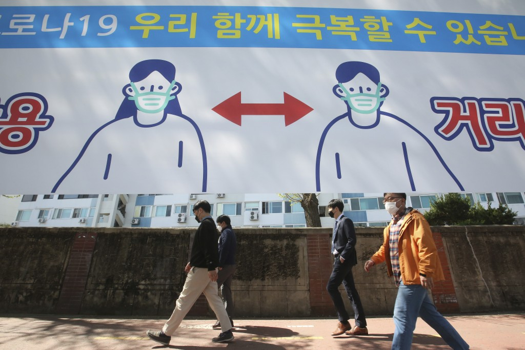 People wearing face masks pass by a banner displaying precautions against the coronavirus on a street in Seoul, South Korea, Monday, April 5, 2021. Th...