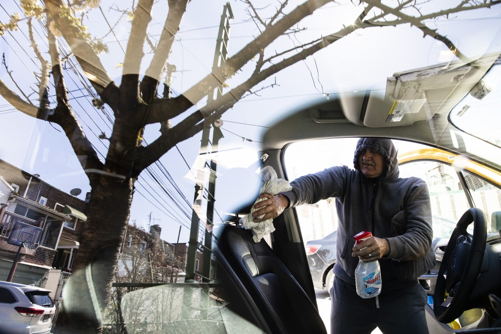 FILE - In this April 6, 2020, file photo, taxi driver Nicolae Hent cleans and disinfects his cab before starting work in New York. A taxi driver's job...