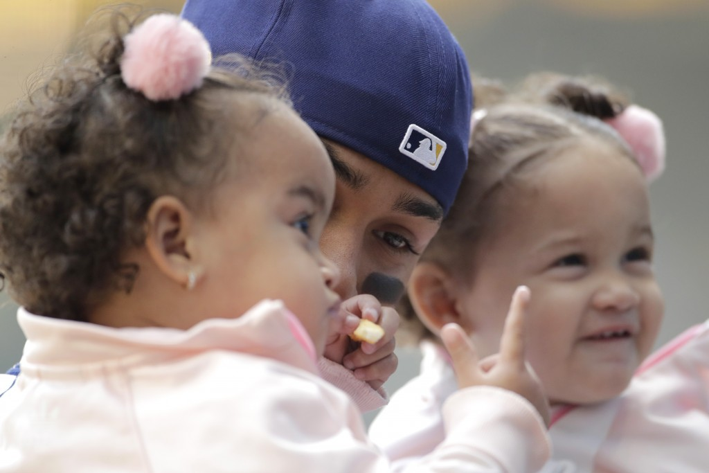 Milwaukee Brewers' Orlando Arcia holds his children before a baseball game against the Minnesota Twins Sunday, April 4, 2021, in Milwaukee. (AP Photo/...