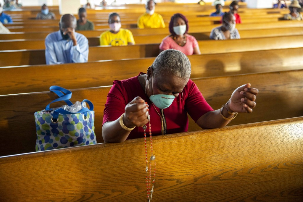 FILE - In this July 12, 2020 file photo, a woman prays during a Mass marking the reopening of places of worship at the Cathedral in Port-au-Prince, Ha...