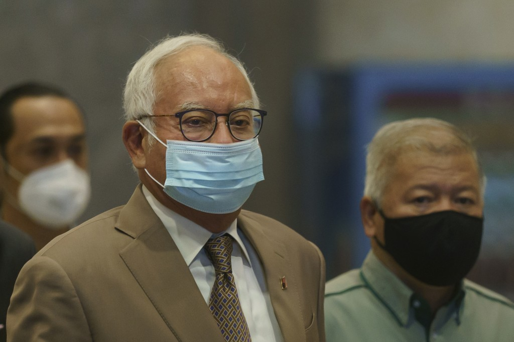 Former Malaysian Prime Minister Najib Razak, center, wearing a face mask arrives at Court of Appeal in Putrajaya, Malaysia, Monday, April 5, 2021. The...