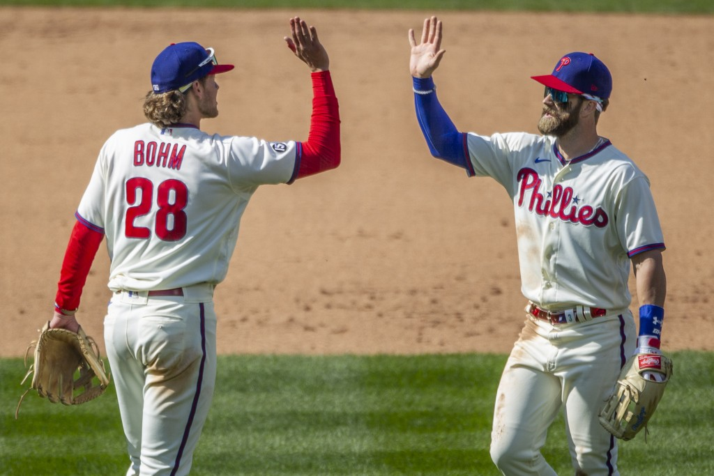 Philadelphia Phillies third baseman Alec Bohm, left, and right fielder Bryce Harper, right, high five after their team defeated the Atlanta Braves in ...