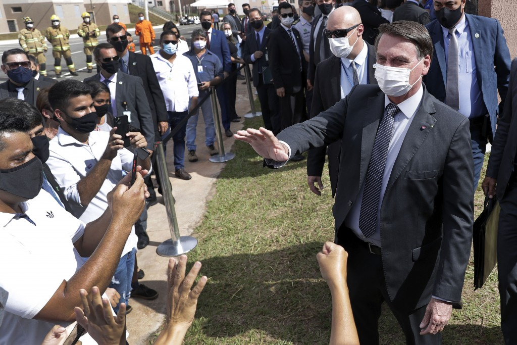 Wearing a mask to curb the spread of the new coronavirus, Brazil's President Jair Bolsonaro greets people after a ceremony to deliver affordable homes...