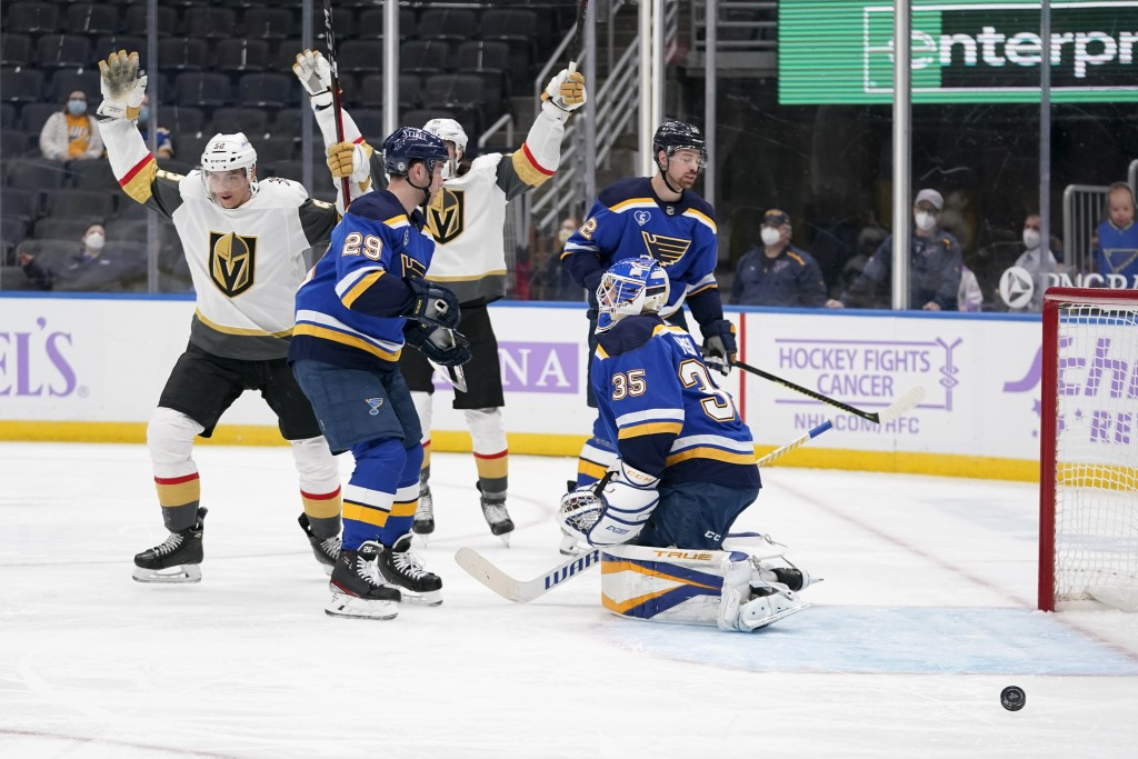 Vegas Golden Knights' Tomas Nosek, left, celebrates after scoring past St. Louis Blues goaltender Ville Husso (35) and Vince Dunn (29) during the firs...