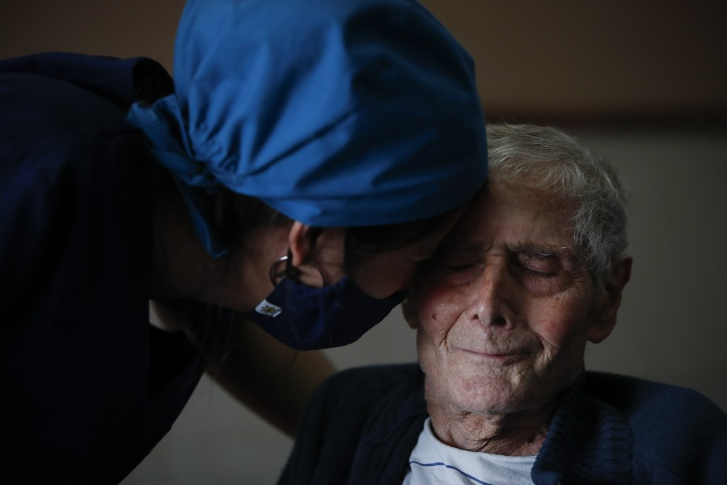 Nurse Rocio Lescano touches foreheads with Victor Tripiana, 86, at the Reminiscencias residence for the elderly in Tandil, Argentina, Monday, April 5,...