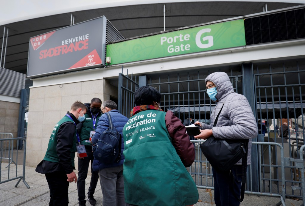 People are guided upon their arrival at the Stade de France stadium to be vaccinated against COVID-19 in Saint-Denis, outside Paris, Tuesday, April 6,...