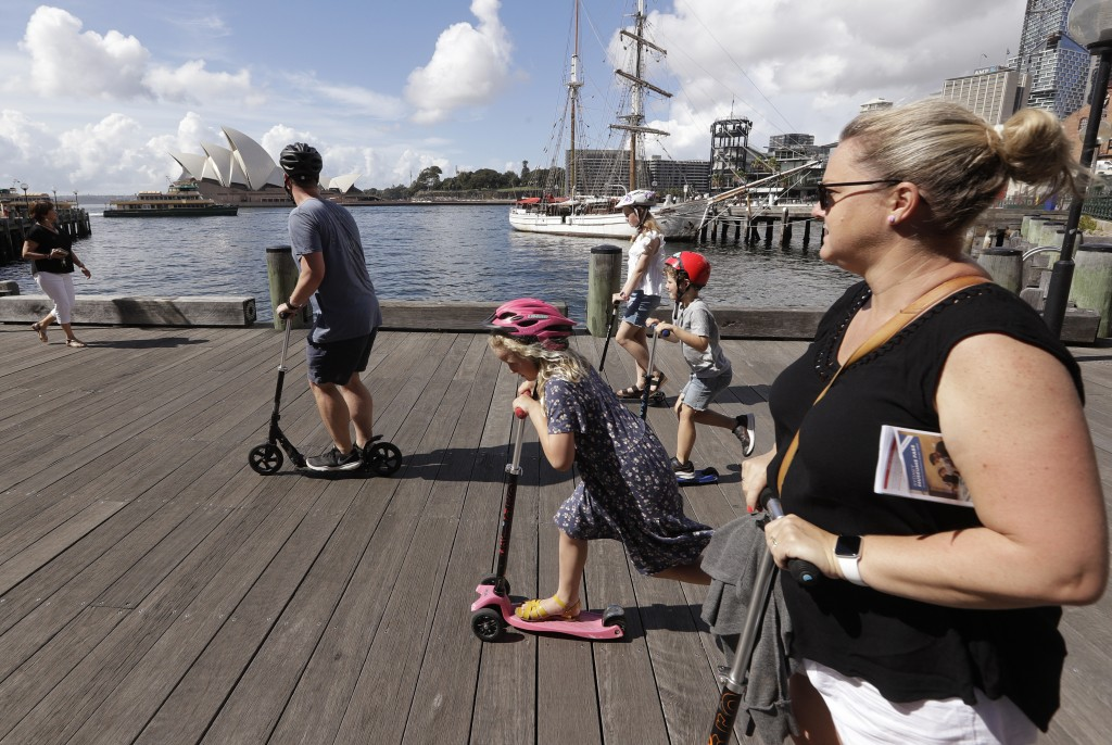A family ride scooters as they travel along a popular boardwalk overlooking the Opera House in Sydney, Australia, Tuesday, April 6, 2021. New Zealand ...
