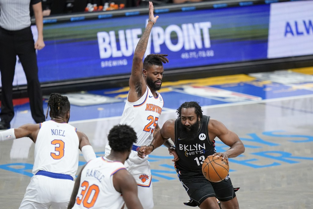 Brooklyn Nets' James Harden (13) drives past New York Knicks' Reggie Bullock (25) during the first half of an NBA basketball game Monday, April 5, 202...