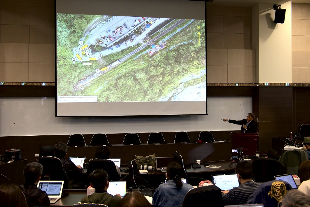Yang Hong-chih, director of Taiwan Transportation Safety Board, at right, points to an aerial view of the site of the train derailment during a press ...