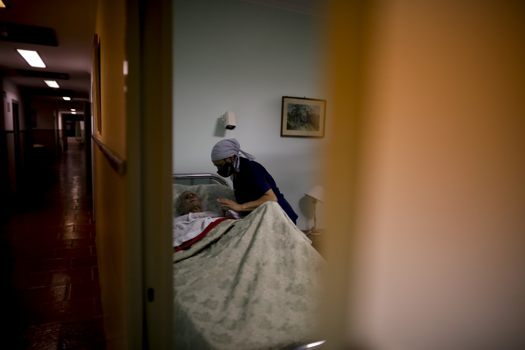 Victor Tripiana, 86, is put to bed by a nurse at the Reminiscencias residence for the elderly in Tandil, Argentina, Sunday, April 4, 2021. Residents h...